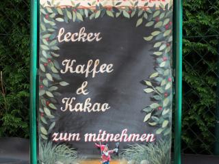 Handgeschriebenes Werbeschild mit Bemalung und dekorativen Elementen.