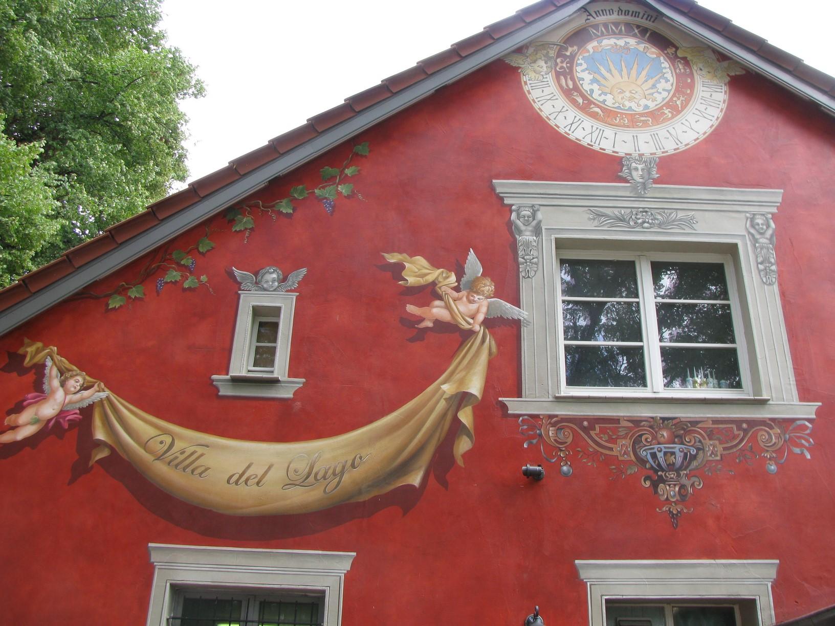 Auf dieser Fassadenmalerei sind kleine Engel die ein Transparent hochheben zu sehen. Ein schönes Beispiel für Wandmalerei.