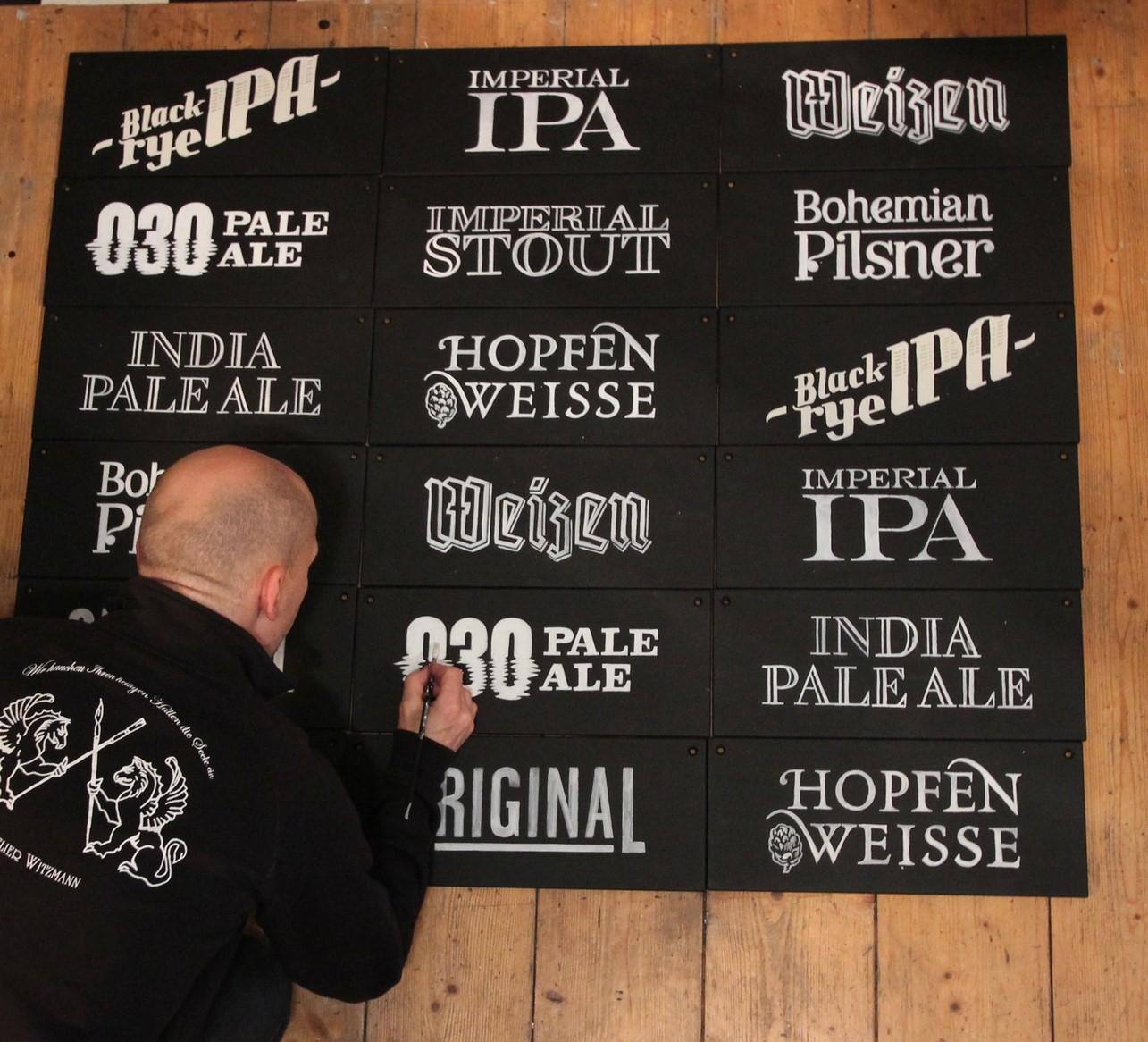 Handgeschriebene Logos auf Holztafeln.